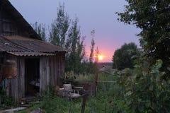 En gammal övergiven stuga i högt gräs på en solnedgång arkivbild
