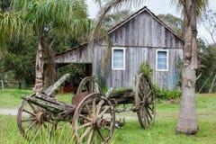 En gammal övergiven vagn med trähus i bakgrunden Royaltyfria Foton