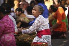 En gammal Balinesekvinna i traditionell kläder på ceremoni för hinduisk tempel, Bali ö, Indonesien arkivbild