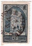 En gammal blå fransk portostämpel med en bild av den reims domkyrkan fotografering för bildbyråer