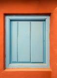 En gammal blå trädörr eller slutare i en orange vägg Arkivbilder