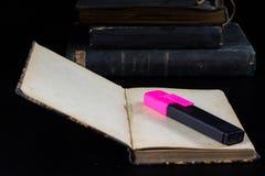 En gammal bok som ligger på en svart tabell I bakgrunden en hög av Arkivbilder