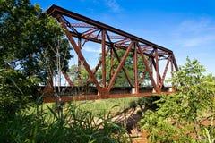 En gammal bråckbandjärnvägbro som korsar en liten vik Royaltyfri Foto