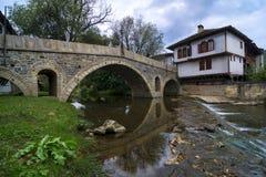 En gammal bro över en liten flod med en vattenfall och ett hus Arkivbild