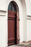 En gammal brun dörr som är prickig på ett hus Royaltyfria Foton