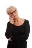 En gammal dam i glasögon trycker på hennes framsida. royaltyfria bilder
