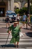 En gammal dam korsar boulevarden framme av Carlton Hotel, Cannes arkivbild