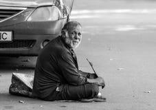 En gammal fattig ledsen mantiggeri på en trottoar nära det Bucharest centret Royaltyfri Fotografi