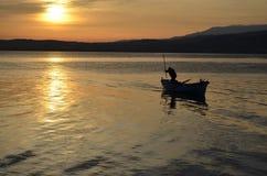 En gammal fiskare på sjön på soluppgång arkivbilder