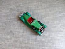 en gammal grön bilmodell på en grå bakgrund Arkivbilder