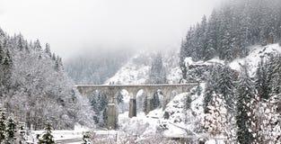 En gammal iconic viaduktbro spänner över en snöig vinterflod arkivbilder