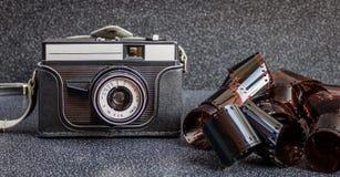 En gammal kamera och filmband Royaltyfri Foto