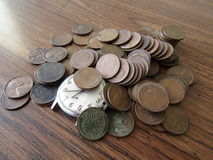 En gammal klocka i en hög av gamla vetepenies, tid är pengar arkivbild