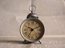En gammal klocka på en tabell fotografering för bildbyråer