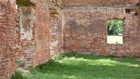 En gammal kollapsad byggnad av röd tegelsten grön lawn stock video