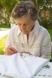 En gammal kvinna broderar på den vita filten Arkivfoto