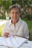 En gammal kvinna broderar på den vita filten Arkivbild