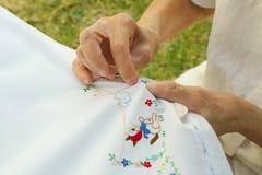 En gammal kvinna broderar på den vita filten Royaltyfri Foto