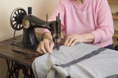 En gammal kvinna för vitt hår syr på en gammal symaskin Anpassa av en gammal sömmerskakvinna Fotografering för Bildbyråer