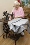 En gammal kvinna för vitt hår syr på en gammal symaskin Anpassa av en gammal sömmerskakvinna Arkivbilder
