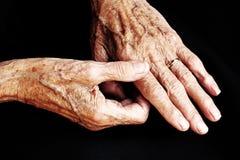 En gammal kvinna har att smärta i hans händer arkivbilder
