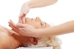 En gammal kvinna har en massage. Spa begrepp. Royaltyfria Foton