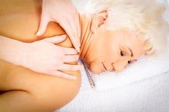 En gammal kvinna har en massage Tvål-, handduk- och blommasnowdrops royaltyfri bild
