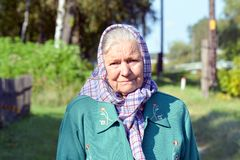 En gammal kvinna i en halsduk Stående av ett ensamt anseende för gammal kvinna i en by Royaltyfria Bilder