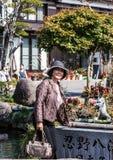 En gammal kvinna i Tokyo Japanskt folk som går på gatan royaltyfri bild