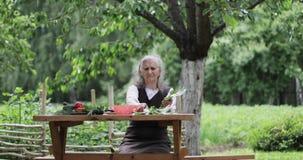 En gammal kvinna med grått hår sitter på en tabell i trädgård- och innehavgräsplansidorna av sallad arkivfilmer