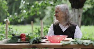 En gammal kvinna med löst grått hår sitter på en tabell i trädgården stock video