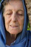 En gammal kvinna med stängda ögon och det dolda huvudet Royaltyfri Fotografi