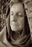 En gammal kvinna med stängda ögon och det dolda huvudet Royaltyfri Foto