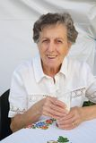 En gammal kvinna och ett exponeringsglas av mjölkar Arkivfoton