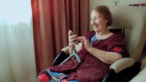 En gammal kvinna skriver ett meddelande och blickar på fotona på hennes nya smartphone Mormor med djupa skrynklor inomhus Lycklig arkivfilmer