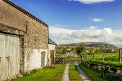En gammal ladugård i Cumbria på en solig dag med en träport och avlägsna kullar Royaltyfria Foton