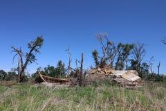 En gammal lantgårdbyggnad och omgeende träd som förstörs av en tromb Royaltyfria Bilder