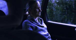 En gammal ledsen kvinna med djupa skrynklaritter i bilen på natten lager videofilmer
