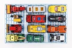 En gammal leksakbilsamling som lagras i en plast- behållare Arkivfoto