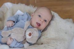 En gammal månad behandla som ett barn pojken som ligger med nallebjörnen royaltyfria foton