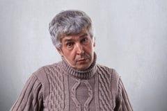 En gammal man med skrynklor som har den iklädda tröjan för grått hår som har förstående uttryck som isoleras över vit bakgrund mo royaltyfri foto
