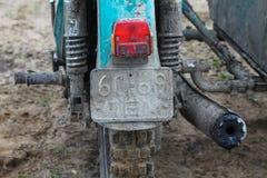 En gammal motorcykel - den partiska sikten av smutsigt särar tillbaka med baklyktan, hjulet och ljuddämparen på av vägen Arkivfoto