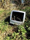 En gammal och omodern datorbildskärm som har dumpats i ofruktbar mark i tippa för en fluga eller förlorad begreppsbild royaltyfri fotografi