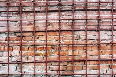 En gammal och Time-sliten vägg för röd tegelsten bak ett metallgaller fotografering för bildbyråer