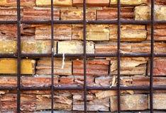 En gammal och Time-sliten vägg för röd tegelsten bak ett metallgaller arkivfoto