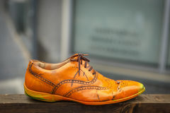 En gammal orange sko på en träplanka Royaltyfri Foto