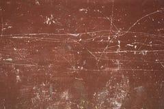 En gammal röd-brunt vägg med djupa vita skrapor och fläckar ungefärlig textur royaltyfri fotografi