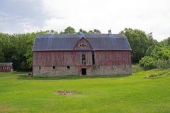 En gammal röd ladugård med ett blått tak Arkivfoto