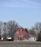 En gammal röd ladugård och ett fåfängt för väder Arkivbild
