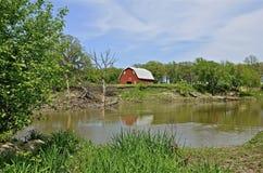 En gammal röd ladugård på flods kant Fotografering för Bildbyråer